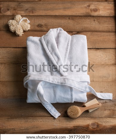 bathrobe bath soap and loofah brush behind wooden table