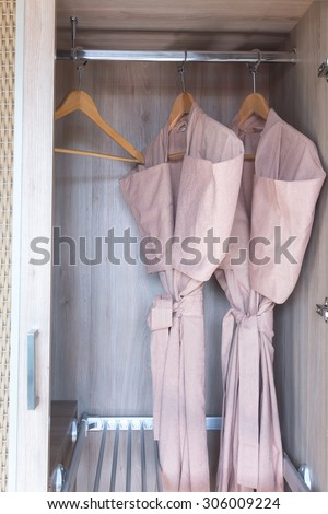 bathrobe with wooden hangers in clotheset