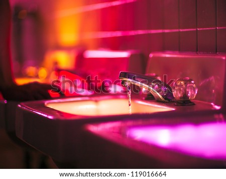 Bathrom taps lit in bright colors at a party - stock photo