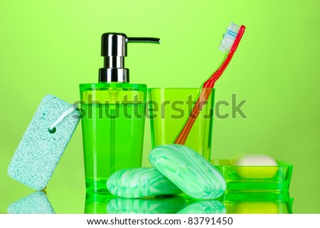 bathroom accessories and soap on green background