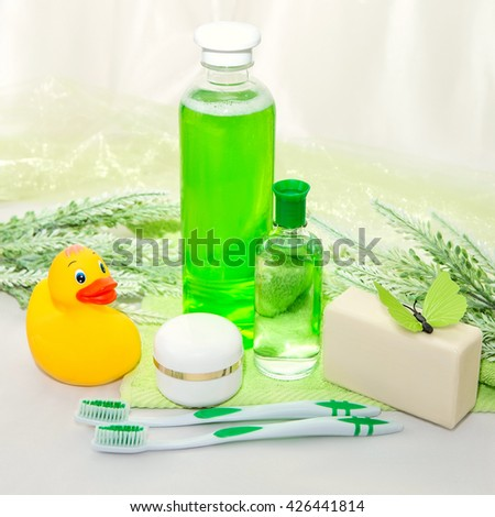 bathroom accessories on a green towel rubber ducky soap and lotion