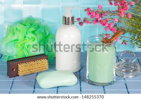 Bathroom accessories still life in clean fresh green and aquamarine with bathsalts, a pump dispenser, nail brush, soap and net sponge on a tiled surface with pink blossom - stock photo