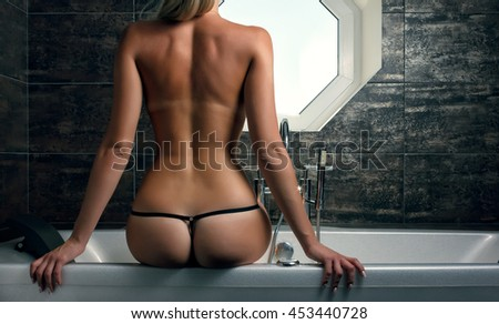 Bathroom. Back view of sexy naked woman sitting on a bath - stock photo