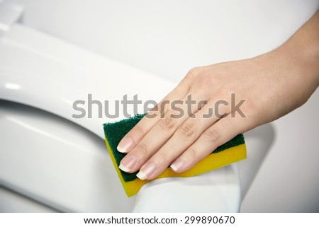 Bathroom cleaning concept, young woman cleaning a toilet seat with a sponge, closeup view of the hand - stock photo