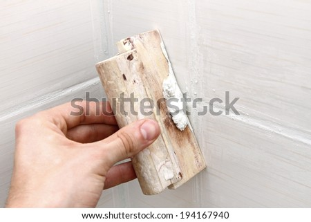 bathroom construction - worker applying white grout on tiles - stock photo