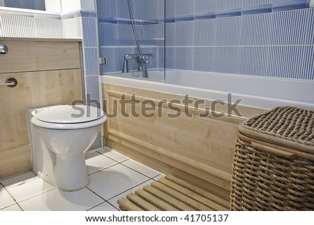bathroom detail with ceramic toilet and laundry basket - stock photo