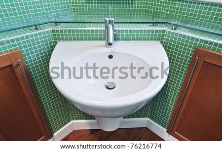 bathroom detail with green mosaic tiles and glass shelves - stock photo