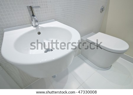 Bathroom detail with hand wash basin and toilet with mosaic tiles - stock photo