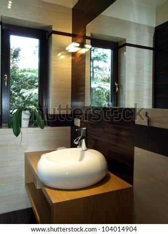 Bathroom equipment: original white sink on wooden cupboard - stock photo