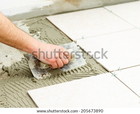Bathroom floor tiling by manual worker. - stock photo