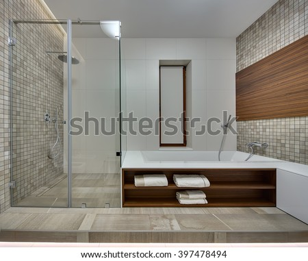 Bathroom in a modern style with light tiles on the back wall. Side walls is decorated with brown-beige mosaic  and a wooden panel. On the right there is a white bath with wooden niches. There are - stock photo