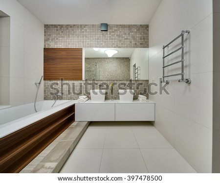 Bathroom in a modern style with light tiles on the walls and floor. On the left there is a white bath with wooden niches on the right side. On the right wall there is a towel rail. On the back wall - stock photo