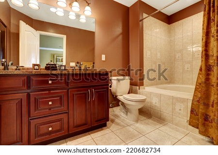 Bathroom in brown color with beige tile trim. Modern wooden cabinet with granite top and mirror - stock photo
