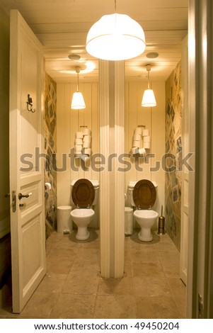 bathroom in public place with two toilets - stock photo
