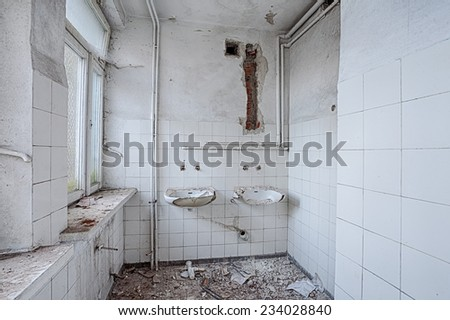 Bathroom in the destroyed building - stock photo