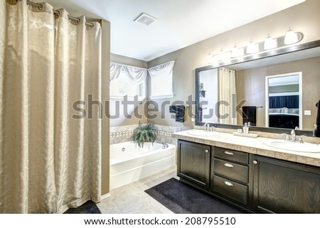 Bathroom interior in light grey tones with black vanity cabinet with large mirror. - stock photo