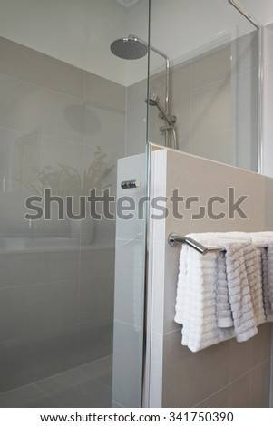 Bathroom interior in neutral tone with tiles, shower head and towels.