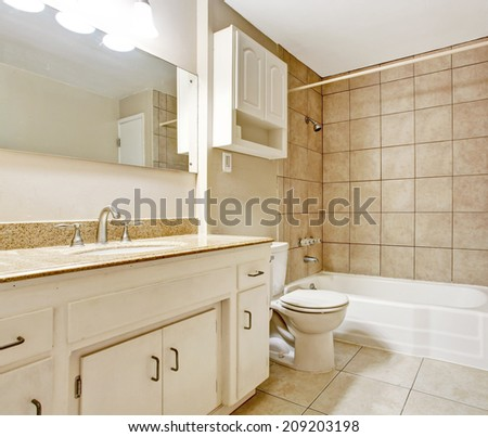 Bathroom interior in soft mocha color with whited old cabinets - stock photo
