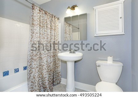 Bathroom interior. Pastel blue walls, white appliances: washbasin stand and a toilet , mosaic tile wall trim in the shower. Northwest, USA