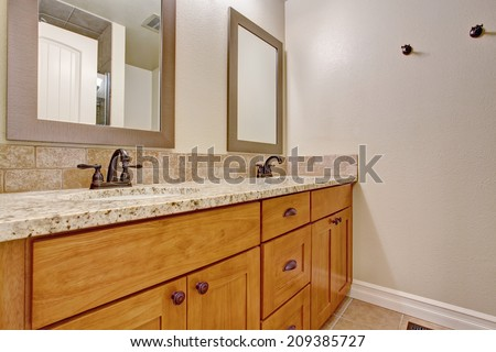 Bathroom interior. View of bathroom vanity cabinet with granite top and two mirrors