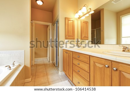 Bathroom interior with beige tiles and wood cabinets. - stock photo
