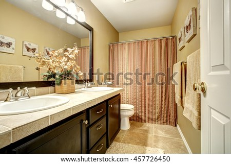 Bathroom interior with dark brown vanity cabinet, tile floor and striped curtain - stock photo