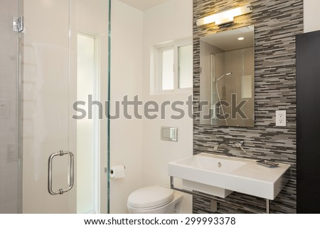 Bathroom interior with Glass shower and Linear Mosaic Tiles with rectangular style bathroom sink. - stock photo