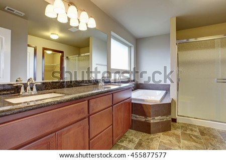 Bathroom interior with vanity cabinet, two sinks, granite counter top and white bath tub