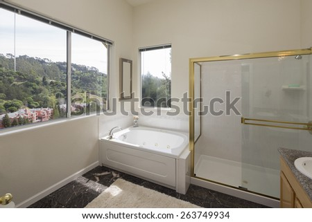 Bathroom interior with view window, whirlpool, gold framed shower and appliances plus black marble floor. - stock photo