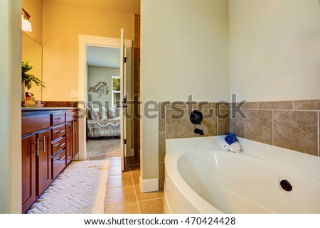 Bathroom interior with white bath tub, tile floor and vanity cabinet. Northwest, USA