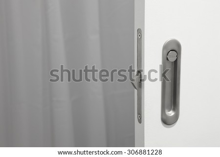 Bathroom metallic doorknob with lock over a white door. Horizontal