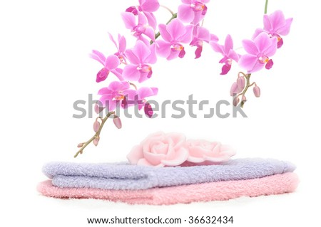 Bathroom set with two towels, two rose petal shaped pieces of soap and a decorative pink orchid - stock photo