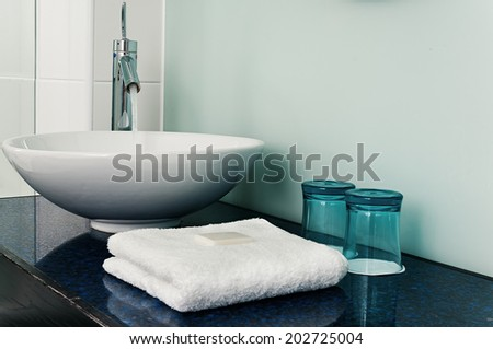 Bathroom sink counter towels water glass blue - stock photo