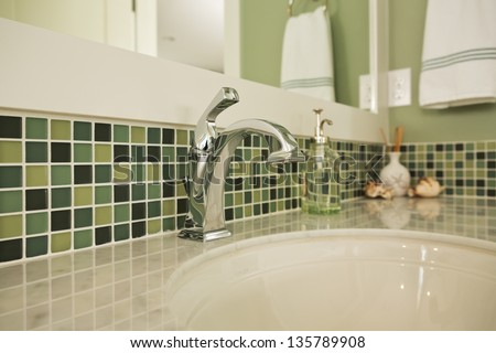 Bathroom sink of an upscale home/Horizontal shot of an elegant, polished and clean sink in an upscale home with colorful green tiling - stock photo