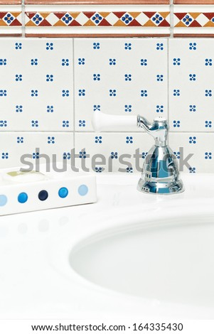 Bathroom sink with tiled backsplash. Cheerful blue and white theme. - stock photo