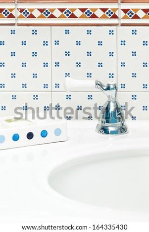 Bathroom sink with tiled backsplash. Cheerful blue and white theme. - stock photo