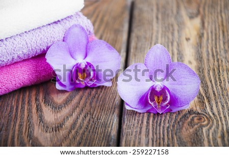Bathroom soft and fresh towels with orchid on a wooden background - stock photo