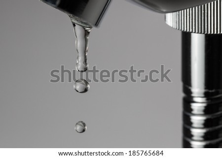 Bathroom tap leaking water drops on grey background - stock photo
