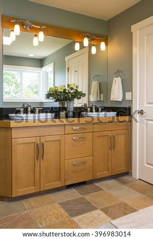 Bathroom vanity with wood cabinets, double sinks, slate tile floors and accent lighting in contemporary upscale home interior - stock photo