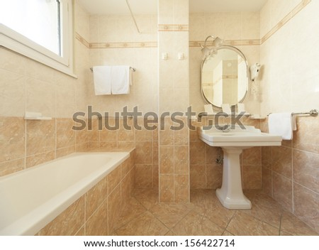 bathroom with beige tiles and decorations - stock photo