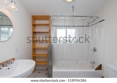 Bathroom With Cabinets And Round Mirror. View Of Bath Tub With Transparent Shower  Curtain.