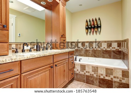 Bathroom with close up view of cabinets with mirror and bath tub with tile wall trim and candles - stock photo