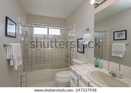 Bathroom with Glass shower and white counter tops plus bath top. - stock photo