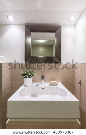 Bathroom with glossy white and brown tiles, new basin and mirror