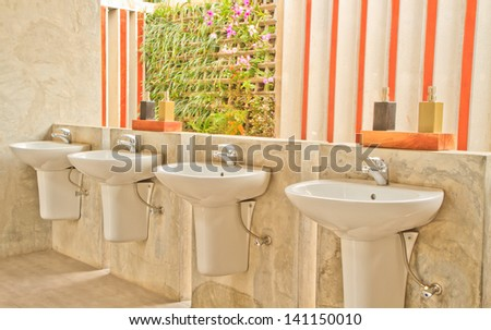 Bathroom with hand washing liquid on color wall background - stock photo