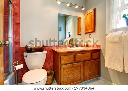 Bathroom with red tile wall trim, old wooden cabinet and white toilet - stock photo