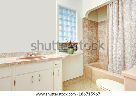 Bathroom with white cabinets, mirror. View of beige bath tub with curtains