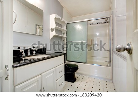 Bathroom with white vanity with black counter top and black toilet. Bathroom has tub with glass door - stock photo