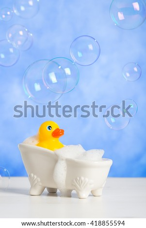 Bathtime fun with rubber duck in bath tub with floating bubbles