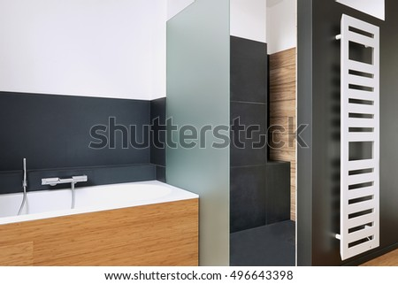 Bathtub and shower in tiled bathroom with vertical radiator